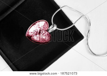 Pink heart shaped medallion in black jewel box closeup