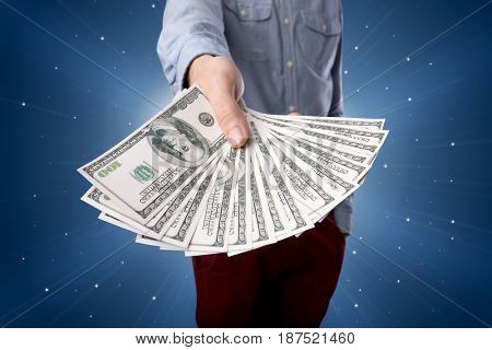Young businessman holding large amount of bills with light beams behind him