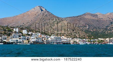 CRETE GREECE - JULY 11 2016: The embankment of a small elite tourist town - Elounda municipality of Agios Nikolaos. View from the sea.