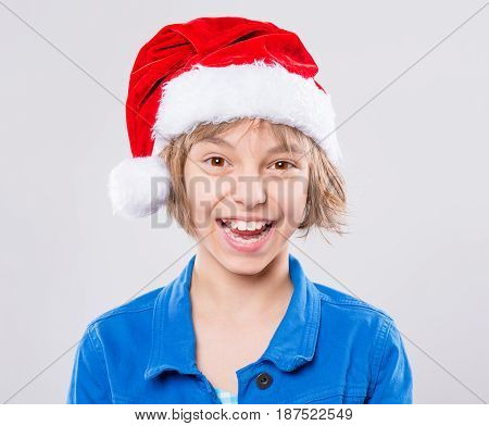 Emotional portrait of attractive caucasian little girl wearing Santa Claus red hat. Funny cute smiling child 10 year old looking at camera on gray background. Winter holiday christmas concept.