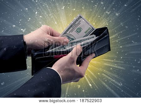 Businessman hand takes out dollar from wallet with fireworks background
