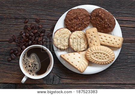 Cup of hot coffee and different shortbread cookies in plate on old wooden table top view