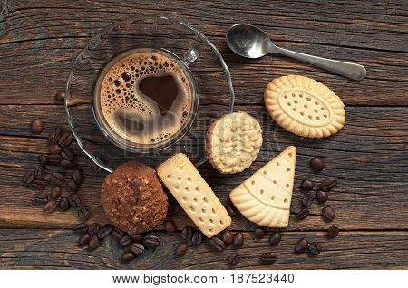 Cup of hot coffee and various shortbread cookies on dark wooden background top view