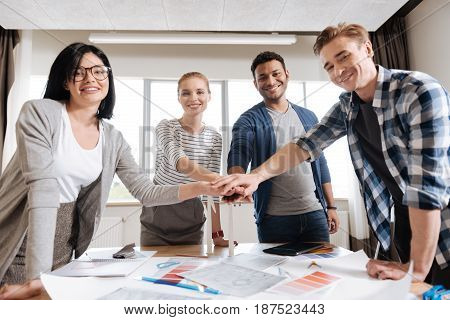 We are the team. Positive happy nice team of engineers standing around the table and holding hand together while preparing to start working