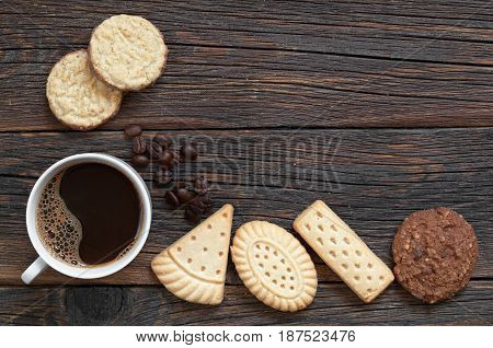 Cup of coffee and different cookies on old wooden table top view. Space for text