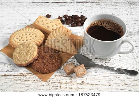 Cup of hot coffee and various shortbread cookies on white wooden table