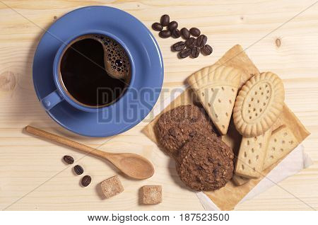 Blue cup of hot coffee and different cookies on wooden table top view
