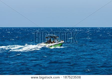 CRETE GREECE - JULY 11 2016: High-speed motor boat with tourists on the sea. View from the sea on the north coast of Crete.