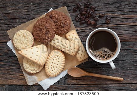 Cup of hot coffee and various shortbread cookies on dark wooden table top view