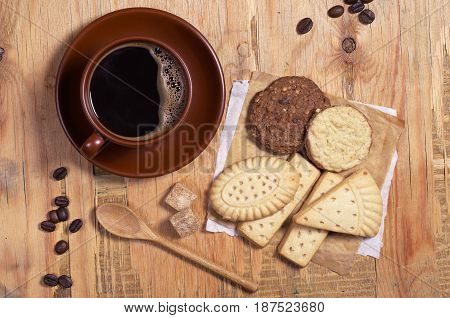 Cup of hot coffee and shortbread cookies on old wooden table top view