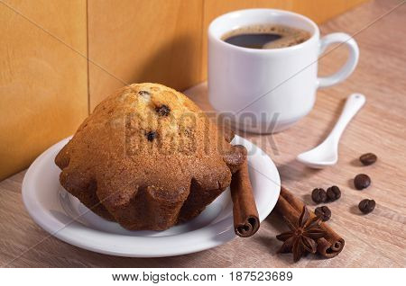 Cupcake with raisins and cup of hot coffee for breakfast on kitchen table
