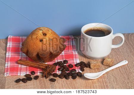 Cup of coffee and cupcake with raisins for breakfast on table