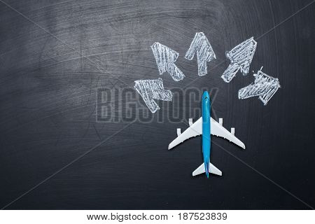 toy airplane over chalkboard background and arrows drawings