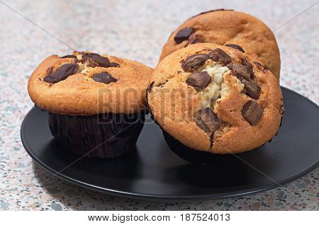 Muffins with chocolate in black plate on table