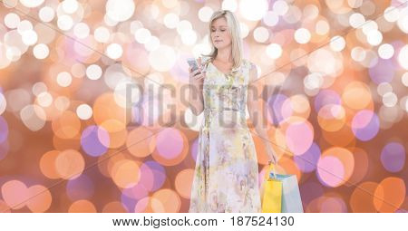 Digital composite of Woman using mobile phone while carrying shopping bags over bokeh