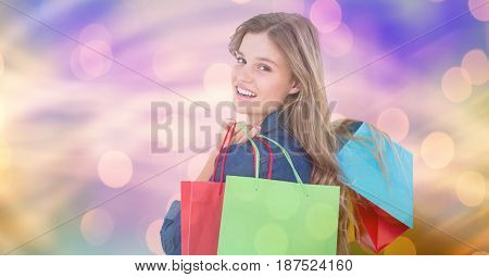 Digital composite of Smiling woman carrying shopping bags over bokeh