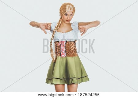 Woman in Bavarian dress with thumbs down.