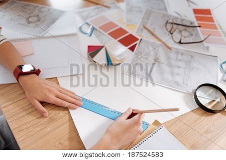 Technical drawings. Professional nice experienced engineer using a pencil and ruler and doing a technical drawing while working on her project
