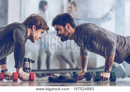 Athletic Young Sportsmen Doing Push Ups With Dumbbells At The Gym, Gym Workout Concept