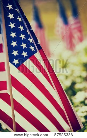 Row of American flags displayed on the street side closeup with shallow depth of field. Vintage filter effects.