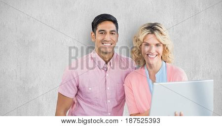 Digital composite of Smiling business people with laptop against wall