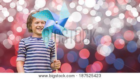 Digital composite of Happy boy holding pinwheel against bokeh