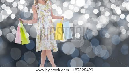 Digital composite of Midsection of woman holding shopping bags over bokeh