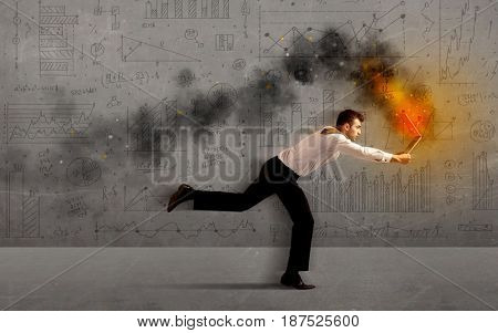 Running business man in a hurry with fire laptop concept