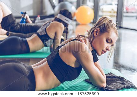 Side View Of Sporty Young People On Yoga Mats Exercising At The Gym