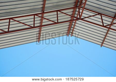 Soft focused picture of Metal sheet roof of factory with blue sky background