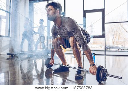 Full length view of muscular sportsman lifting barbell at gym workout