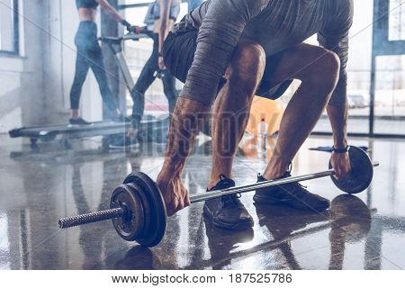 Close-up partial view of muscular sportsman lifting barbell at gym workout