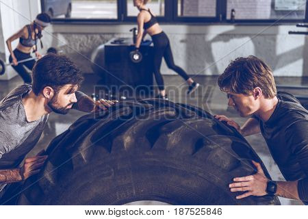 Young sportsmen exercising with big tire at gym workout