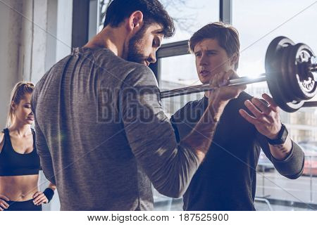 Young sportsmen exercising with barbell and sportswoman standing behind at gym workout