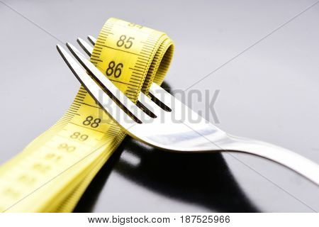 Tape For Measuring Placed Between Tines Of Metal Fork