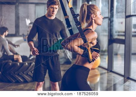 side view of sportive woman exercising with trx gym equipment with trainer near by