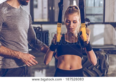 sportive woman exercising with trx gym equipment with trainer near by