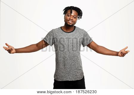 Young handsome african man smiling, looking at camera, posing, gesturing over white background. Copy space.