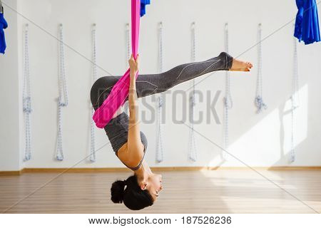 Girl in upside down pose on pink silk hammock, woman does aerial yoga exercises, meditates in calm position with straight legs. Reclining angle position in aerial antigravity yoga.