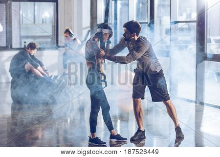 Side View Of Man Cheering Up Sportive Woman In Gym With Trx Equipment