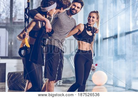 Side View Of Group Of Sportive People Near Trx Equipment In Gym