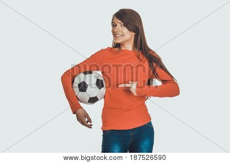 Woman pointing on a soccer ball.