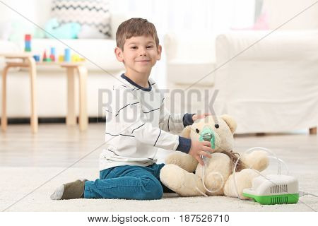 Cute little boy playing with nebulizer at home. Allergy concept