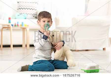 Cute little boy using nebulizer at home. Allergy concept
