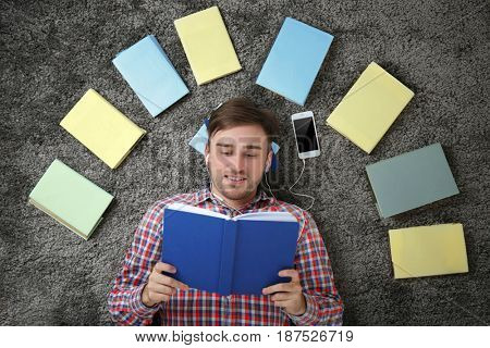 Concept of audiobook. Handsome young man with earphones, books and phone lying on carpet