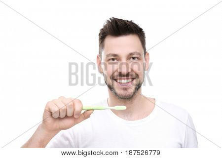 Portrait of handsome young man brushing teeth on white background