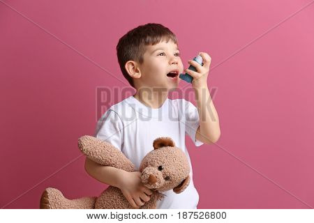 Cute little boy holding inhaler and toy bear on color background. Allergy concept