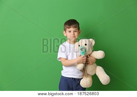 Cute little boy holding nebulizer and toy bear on color background. Allergy concept