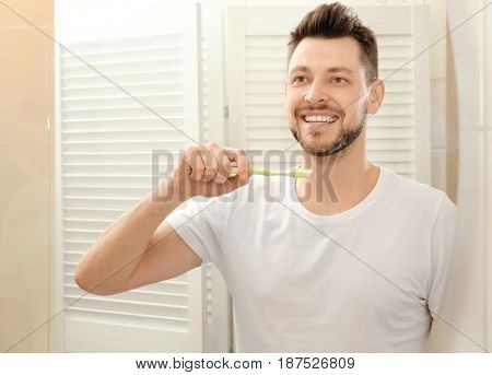 Handsome young man brushing teeth and looking in mirror