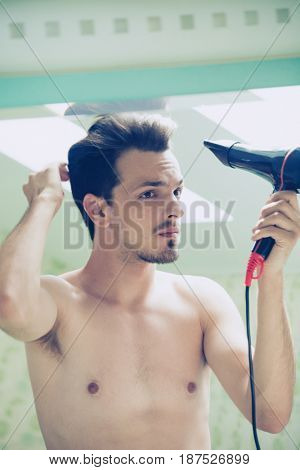young man dry hair with hair dryer reflection in the mirror in bathroom  natural light